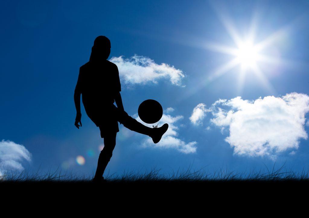 Composición digital de silueta de mujer jugando con pelota contra el fondo del cielo